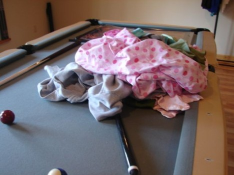 Laundry scattered on pool table